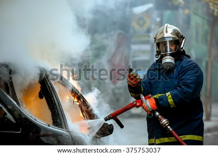 Athens, Greece - February 4, 2016: Firemen fighting a flaming car after an explosion - stock photo