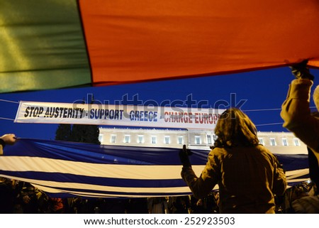 Athens, Greece, February 15, 2015. Protesters wave Greek and Portuguese  flags in front of the parliament during an anti-austerity and pro-government demonstration. - stock photo