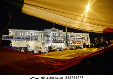 Athens, Greece, February 15, 2015. Protesters wave Italian and Spanish flags in front of the parliament during an anti-austerity and pro-government demonstration. - stock photo