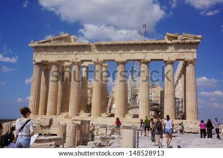 ATHENS, GREECE - JULY 23: Tourists in famous old city Acropolis Parthenon Temple on July 23, 2013 in Athens, Greece. Construction began in 447 BC in the Athenian Empire. It was completed in 438 BC. - stock photo