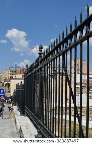 ATHENS, GREECE - JUNE 12, 2015: People resting against metal fence at archaeological site. Street scene in downtown Athens, Greece. - stock photo