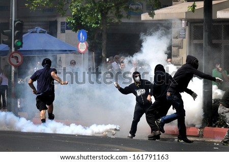 ATHENS, GREECE -MAY 05: Tear gas bombs explodes next to protesters with covered faces who throw stones at riot police during clashes in central Athens, May 05, 2010.   - stock photo