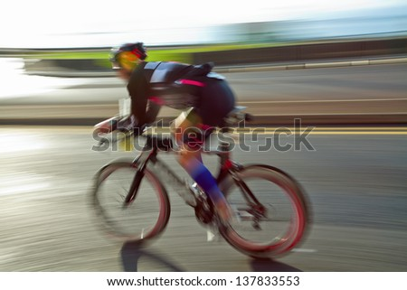 Athlet riding bicycle at sunny day on coastal road, blurred motion - stock photo