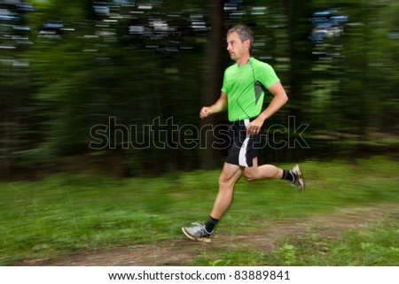 athlet running through the forest - stock photo