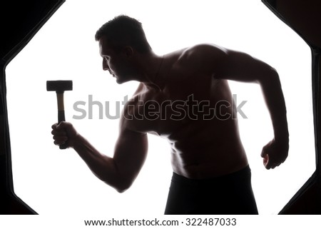 athlete and hammer - a very beautiful young guy with a nice muscle fitness and bodybuilder coach hold in strong arms and big metal hammer - stock photo