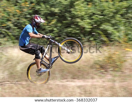 Athlete bicyclist travels at high speed on a mountain bike down the hill. Special effect 'Motion Blur' - stock photo