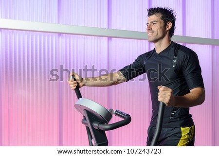 Athlete doing cardio exercise in elliptical machine. Caucasian handsome man training indoor in gym. Copy space. - stock photo