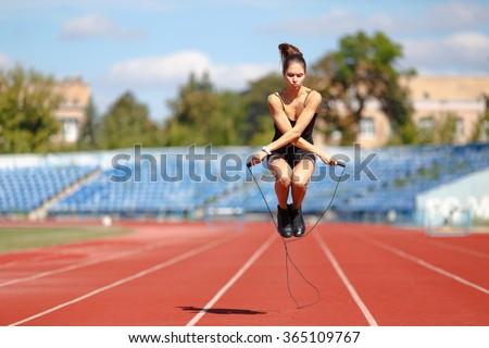 Athlete doing jump exercise on the stadium - stock photo
