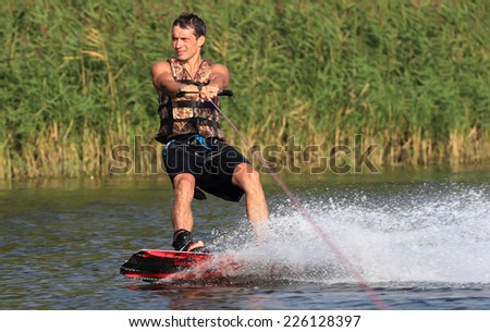 athlete enjoys wakeboarding on the river and looking away - stock photo