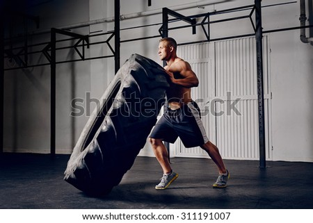 Athlete flipping tire at gym - stock photo