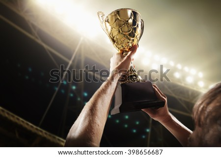 Athlete holding trophy cup - stock photo