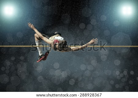 Athlete in action of high jump under rain and bokeh background. - stock photo