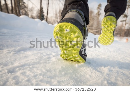 Athlete is running during winter training outside in cold snow weather. Close-up shoes with spikes - stock photo