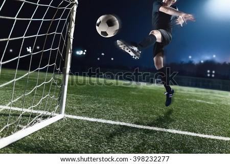 Athlete kicking soccer ball into a goal - stock photo