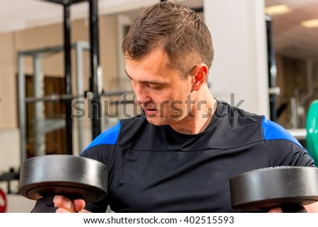 Athlete looks at black heavy weights in the gym - stock photo