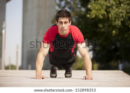 Athlete male at the city park making some push up - stock photo