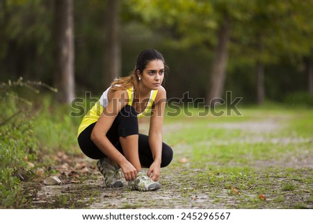 Athlete male at the city park tying the laces of his shoes - stock photo
