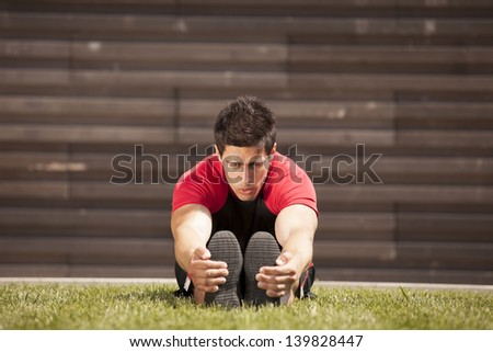 Athlete male at the city park warming and stretching - stock photo