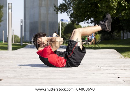 Athlete man at the city park making some abdominals - stock photo
