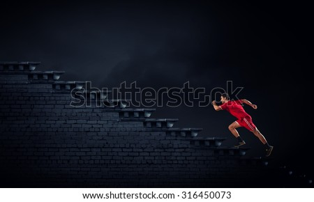 Athlete man in red sport wear running up staircase - stock photo