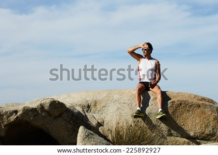 Athlete man in sportswear listening to music on his mobile phone sitting on sea rocks, male runner enjoying the sun and listen to music with headphones, fit man taking break after workout outdoors - stock photo
