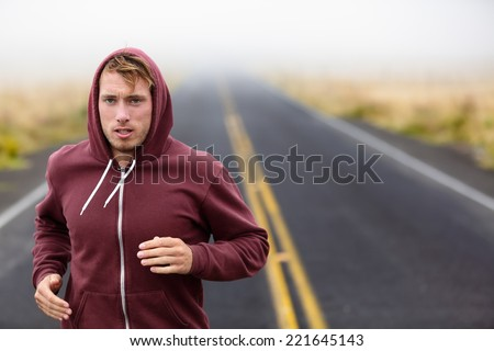 Athlete man running training on road in fall in sweatshirt hoodie in autumn. Male runner training outdoors jogging in nature. - stock photo