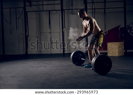 Athlete motivates screaming before barbells exercise at gym - stock photo