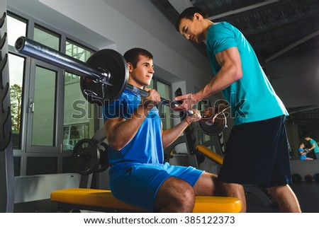Athlete muscular bodybuilder and personal trainer  in the gym training with barbell - stock photo