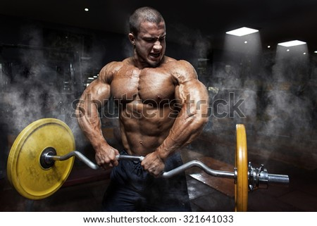 Athlete muscular bodybuilder in the gym training biceps with bar - stock photo