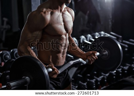 Athlete muscular bodybuilder training biceps curl with dumbbell in the gym - stock photo