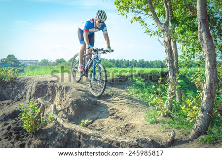 Athlete on a mountain bike rides along the dirt road - stock photo