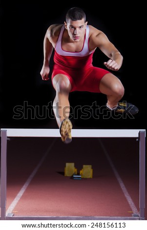 athlete on hurdle in track and field - stock photo