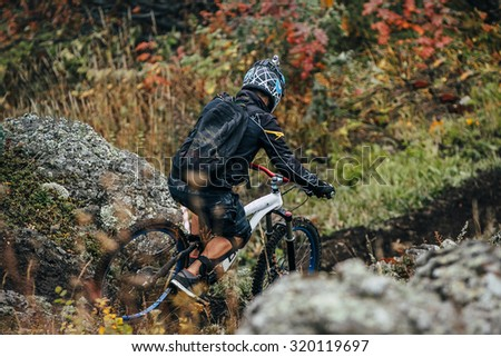athlete on the bike to descend from the mountain along a narrow path between the rocks - stock photo