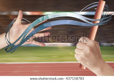 Athlete passing a baton to the partner against view of a stadium - stock photo