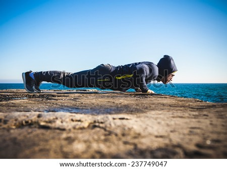 Athlete performing exercises on beach - stock photo