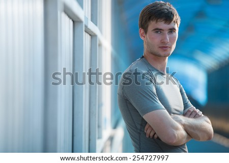 Athlete posing outdoors in city. Standing with hands folded - stock photo