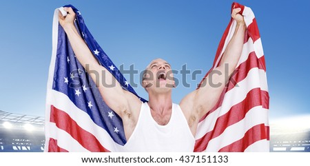 Athlete posing with american flag after victory against large football stadium under bright blue sky - stock photo