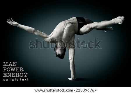 Athlete.Power.Energy.Gym.Men's sports figure.Circus actor stand on one hand  on a black background.Black-and-white image - stock photo