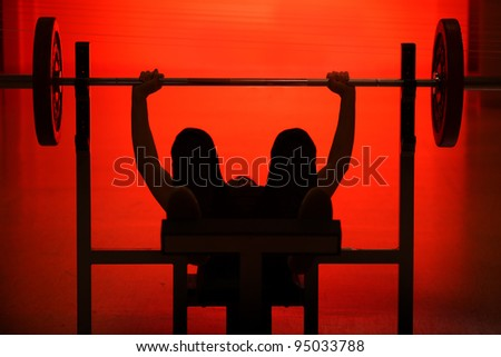 Athlete raising the bar black silhouette on red background - stock photo