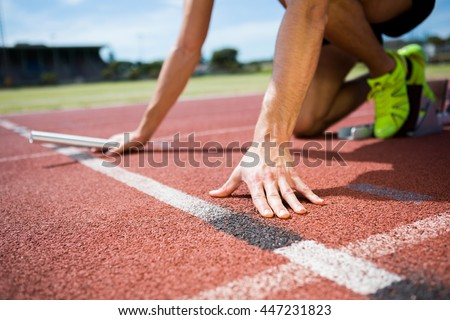 Athlete ready to start the relay race on the running track - stock photo
