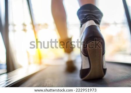 Athlete runner feet running on treadmill closeup on shoe. - stock photo