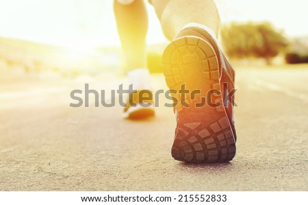 Athlete runner feet running on treadmill  closeup on shoe.Mans fitness with the sun effect of fall autumn colors in the background and open space around him - stock photo