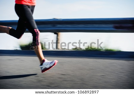 Athlete runner motion blur running on road focus on shoe. woman speed sprint fitness training. - stock photo