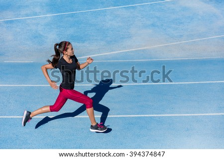 Athlete runner running on athletic track training her cardio. Jogger woman jogging at fast pace for competition race on blue lane at summer outdoor stadium wearing red capri tights and sports shoes. - stock photo