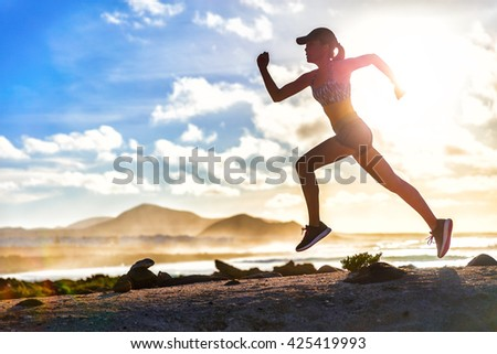 Athlete runner trail running on summer beach. Fit body silhouette of sports Woman in sportswear cap sprinting with energy and motion in outdoors nature training cardio with jogging workout exercise. - stock photo