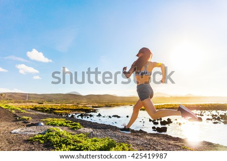 Athlete runner trail running on summer trail beach. Active morning jogging motivation woman sprinting with energy and motion in outdoors nature training cardio race in shorts and sports bra, shoes. - stock photo