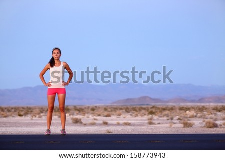 Athlete runner woman resting on road after running on highway in the USA. Beautiful fit fitness girl sweating and relaxing at dusk after a late night run. Mixed race Caucasian Asian female model, 20s. - stock photo