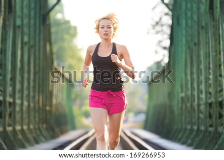 Athlete running on railaway tracks bridge in morning sunrise training for marathon and fitness. Healthy sporty caucasian woman exercising in urban environment; Active urban lifestyle. - stock photo