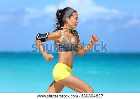 Athlete running woman runner listening to music on her phone sports armband with touchscreen and headphones earphones on summer beach. Fitness girl jogging fast training cardio and glutes. - stock photo