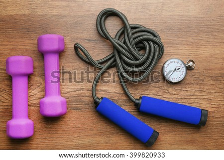 Athlete's set with stopwatch, dumbbells and skipping rope on wooden background - stock photo